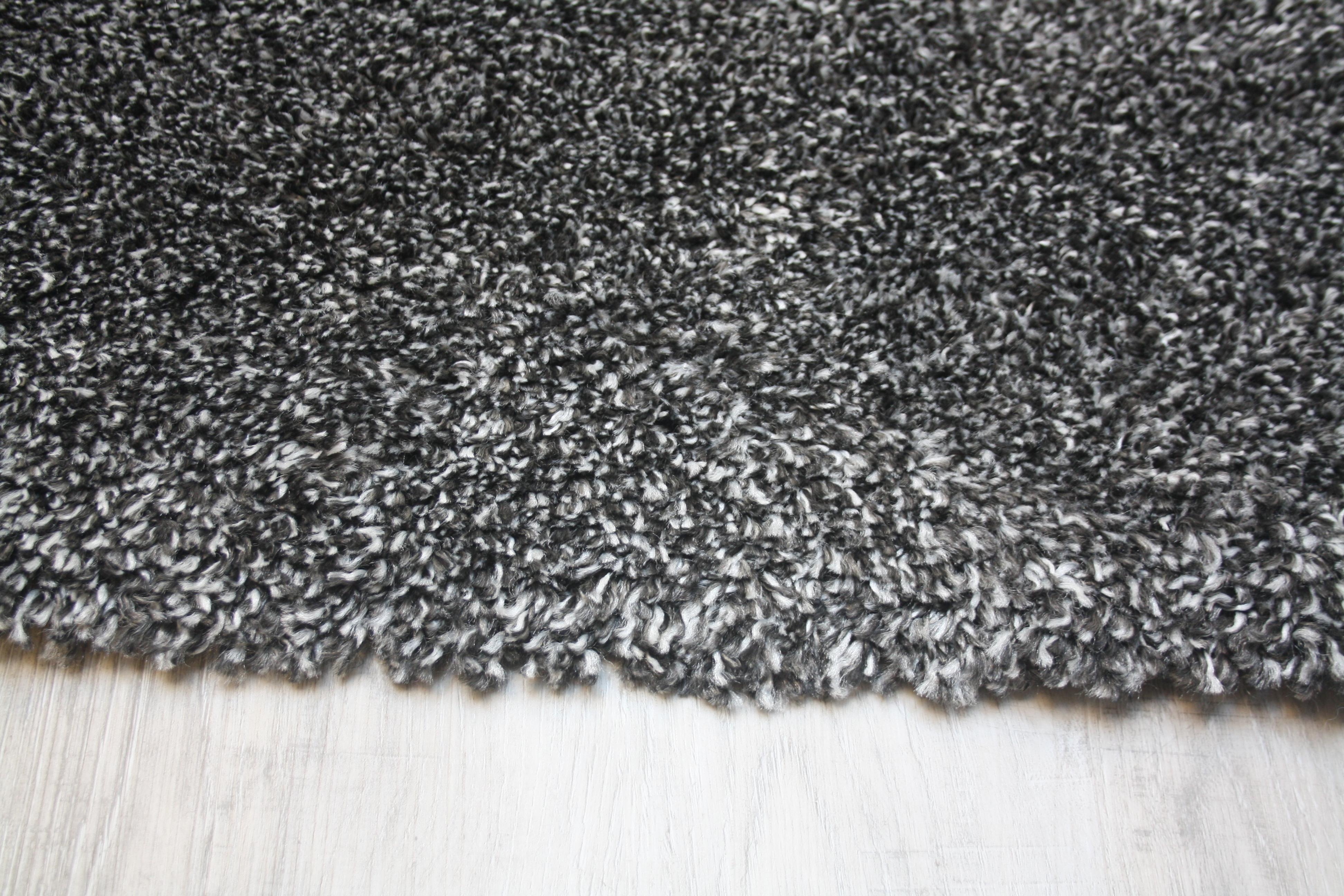Hoogpolig gemêleerd karpet in twee grijstinten.